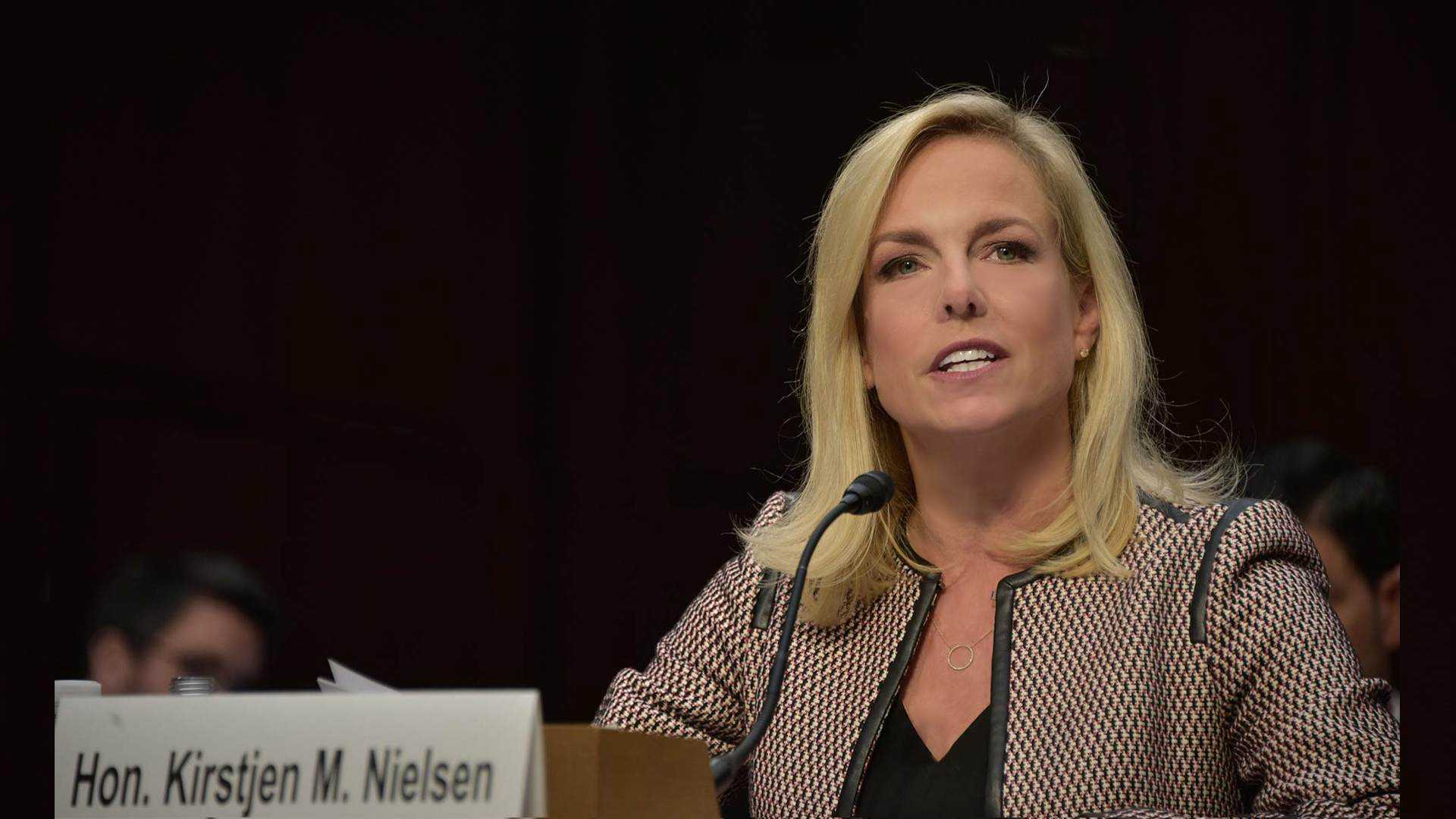 An Image of Kirstjen Nielsen answering questions from congress, she is seated at a table and looking up she is smiling she is a very attractive woman, shoulder lenght lite blonde hair large blue eyes soft features.