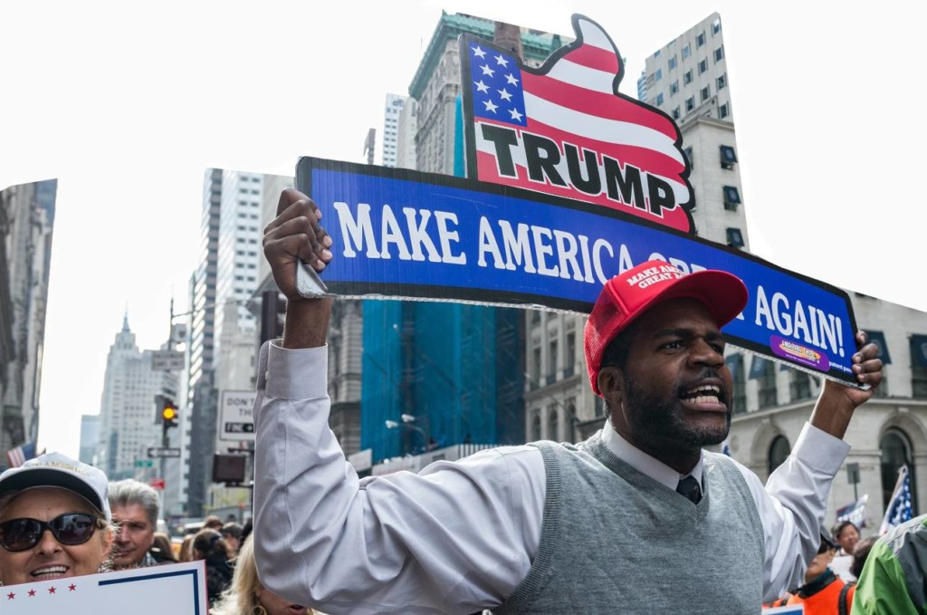 An image of a black man with a red trump hat on and wearing a white shirt with a grey sweater and neck tie, he is marching in a rally to support president trump, he is holding a big sign above his the that sats